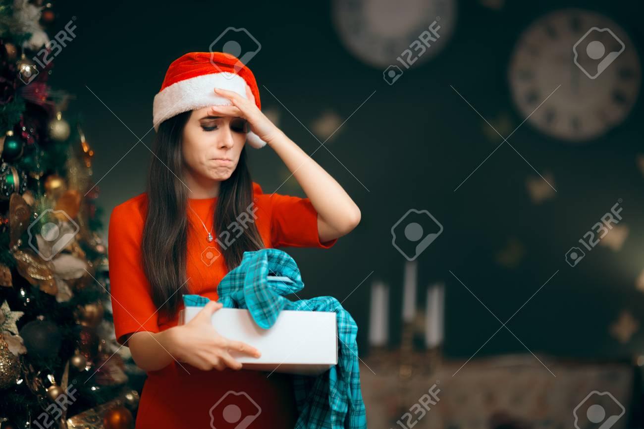 Upset Girl Opening A Bad Christmas Gift Finding Pajamas Inside Stock ...