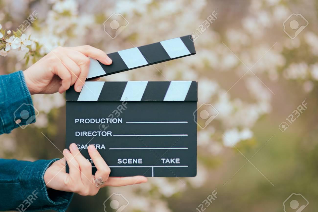 Hands Holding Film Slate Cinema Clapper on Spring Blooming Background - 94389939