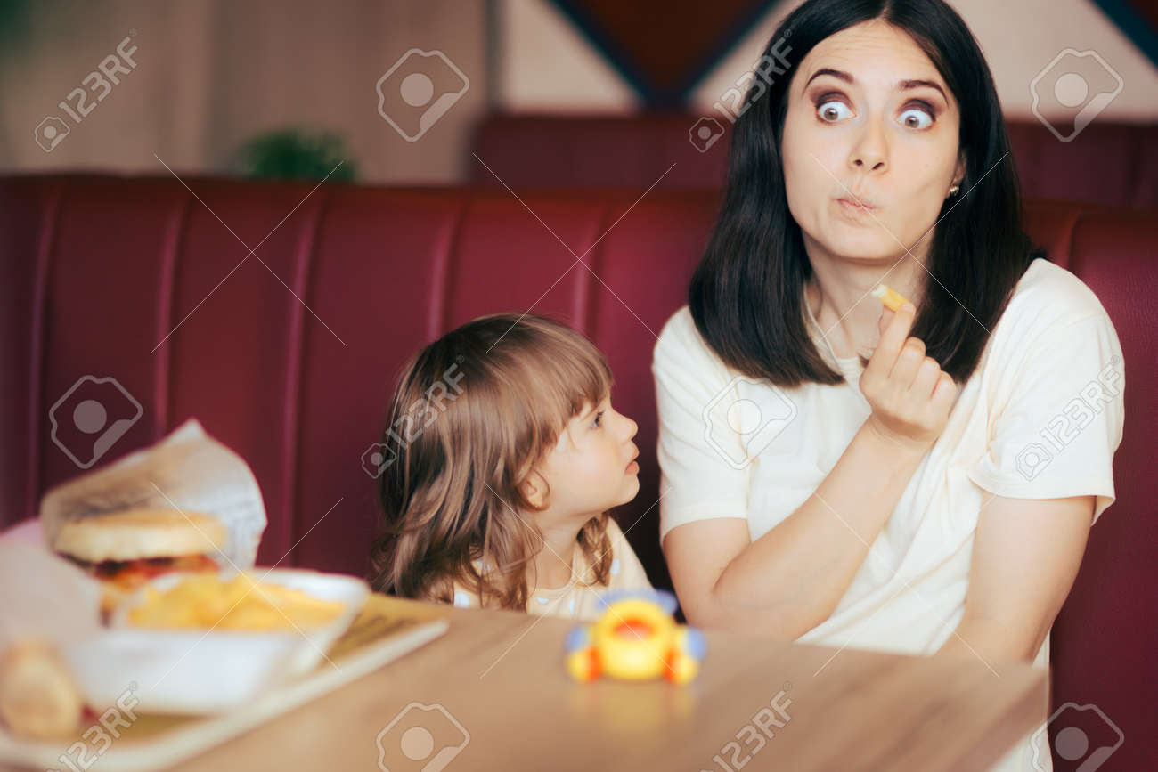 Funny Mom Having French Fries in front of her Toddler Daughter - 171549958