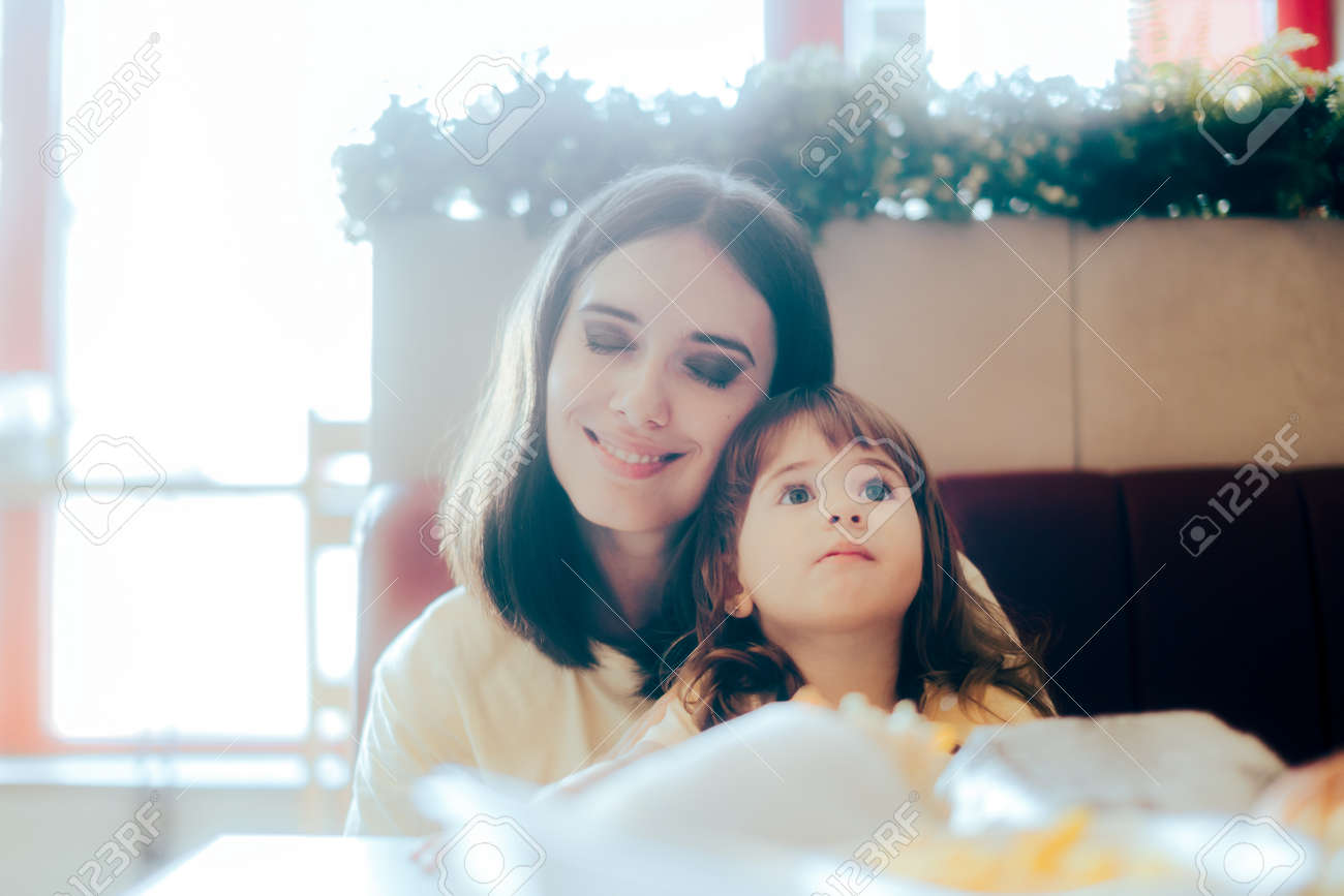 Mother and Daughter Sitting Together in a Restaurant Booth - 171549961