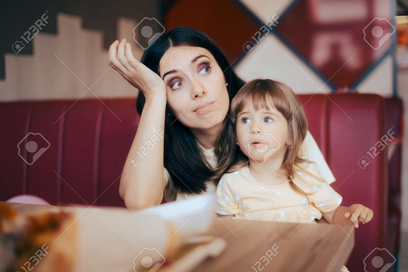 Stressed Mom Sitting with her Child in a Restaurant Booth - 171549953