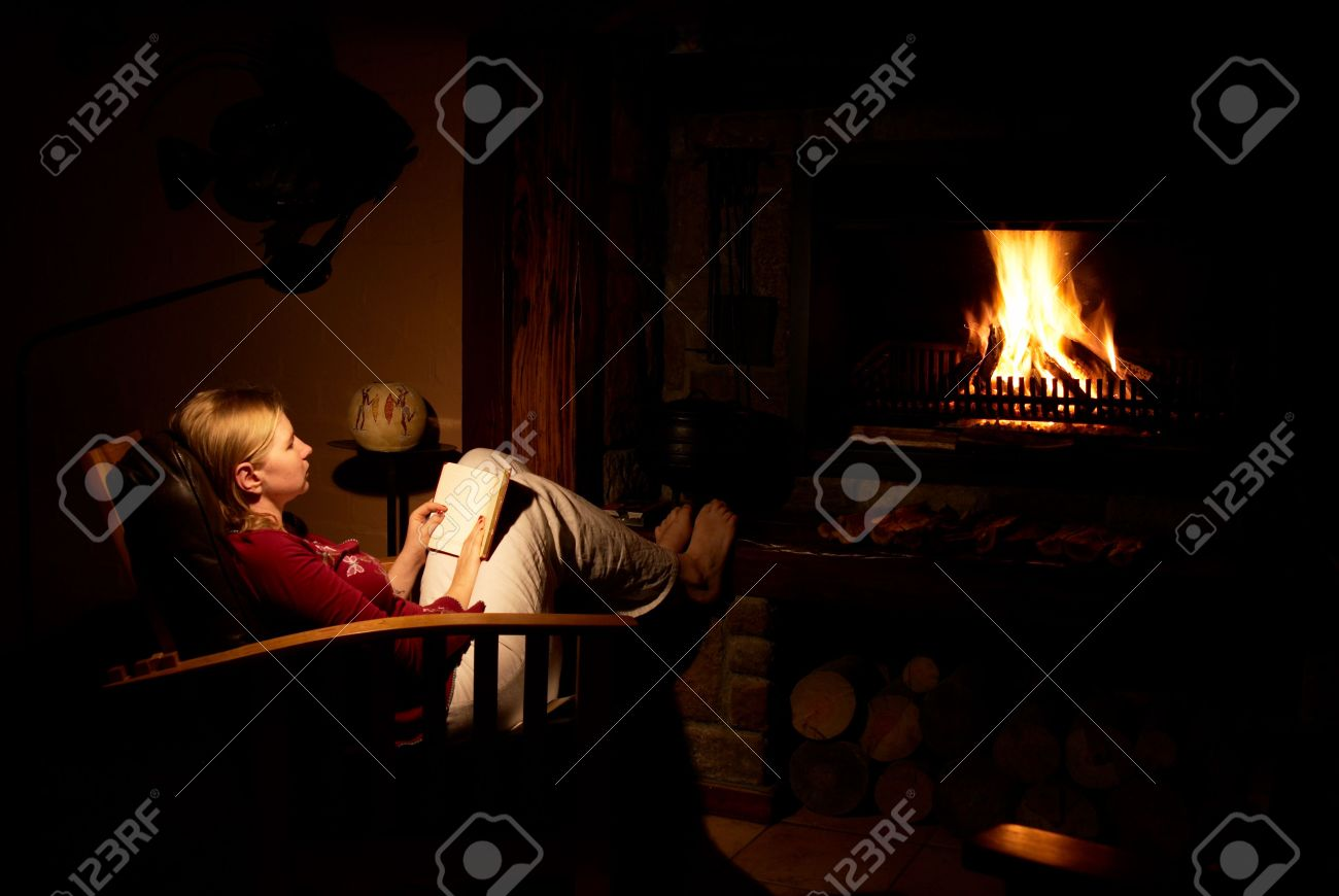 blonde woman sitting infront of the fireplace reading the book