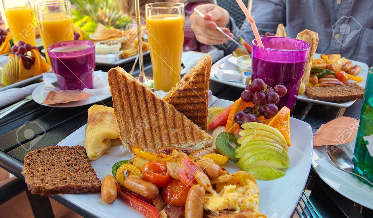Brunch with susages, tomatoes, fruit, toast, coffee and orange juice Stock Photo - 20886328