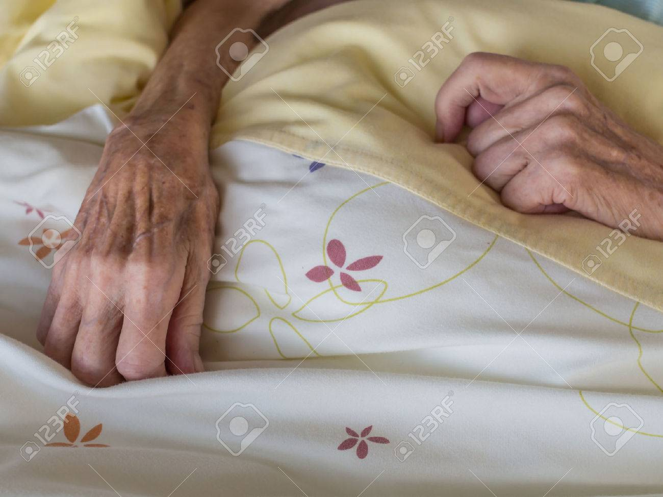 The hands of a very old and skinny woman in bed Stock Photo - 30984884
