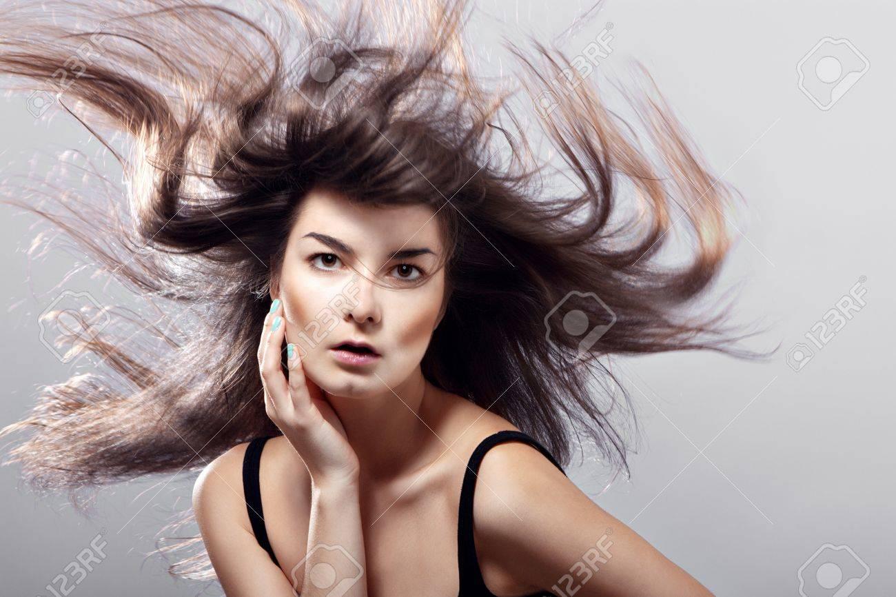 utilisez vous un revitalisant ? 15551007-mode-femme-avec-les-cheveux-au-vent-sur-un-fond-gris-Banque-d'images