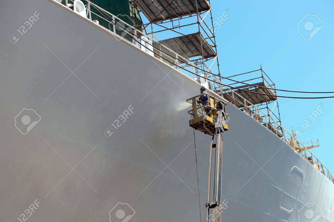Worker painting ship hull using airbrush. Stock Photo - 9809944
