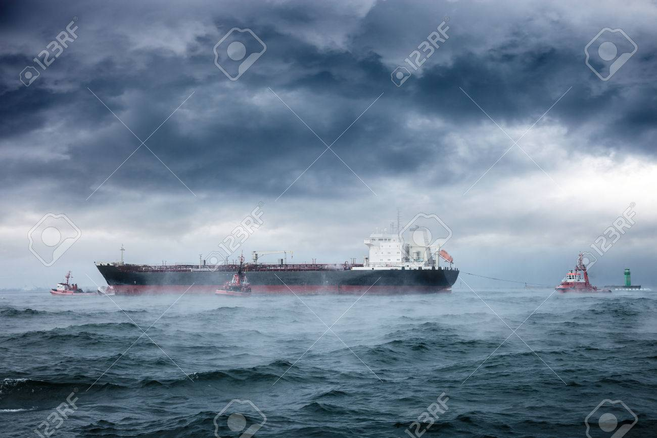 Dark image of tanker and tugboats on sea during a violent blizzard - 25309761