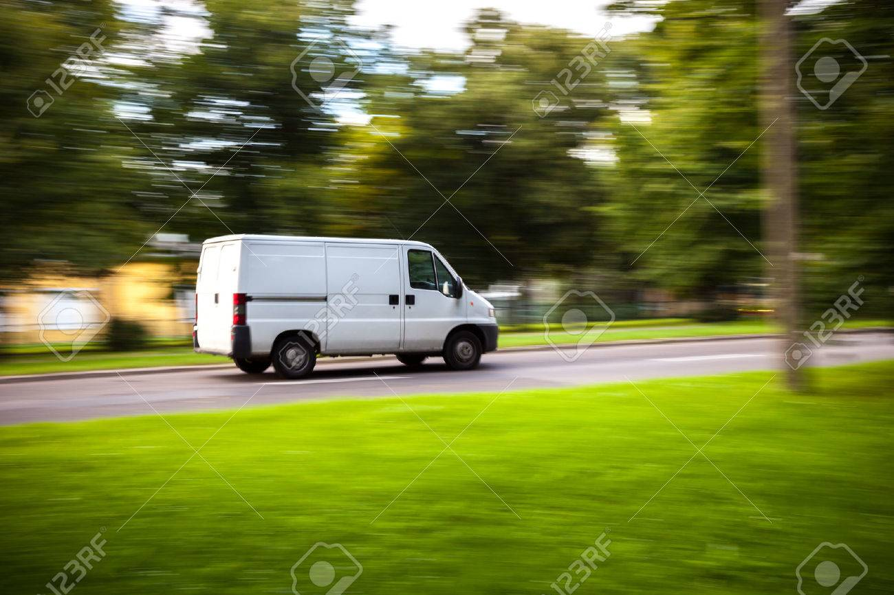 White delivery van speeding on road with blurred countryside panorama in background. - 37513596