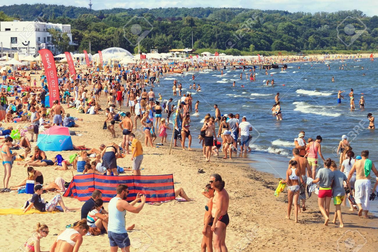 Sandy Beach Scene Of Many People Suntanning Relaxing And Enjoying