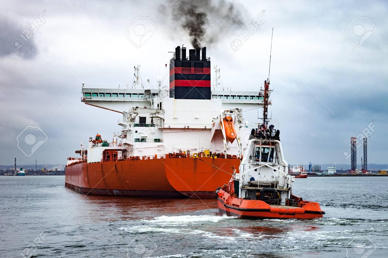 海でタンカー船を曳航するボート...