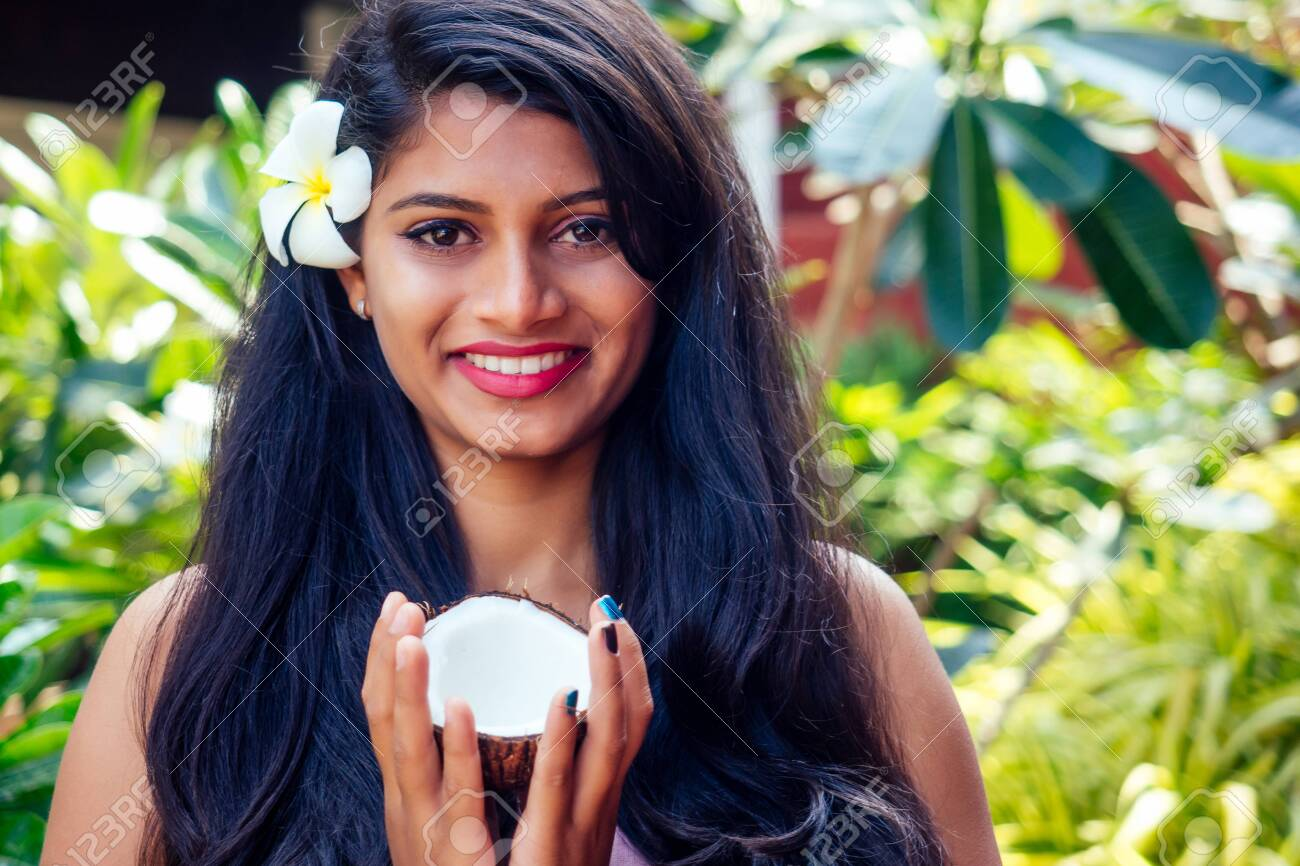 indian woman applying coconut oil dark brunette long hair in a hand on green summer park nature tropical - 130844455