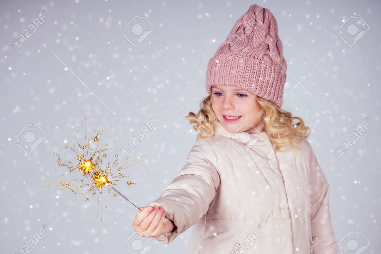 charming little girl in a knitted hat holding fireworks on white background in a studio.Cute blonde child with xmas dream.Happy kid enjoy the fire sparks. new year holidays eve of Christmas a wish - 132637624