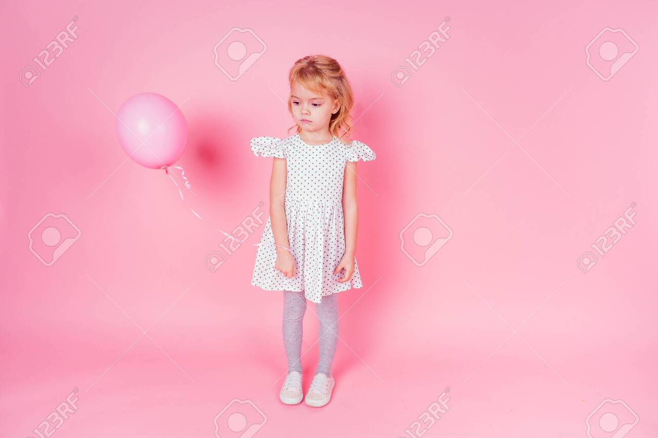 sad little blonde girl in white dress in peas 4-5 year old holding balloon in the studio on a pink background,birthday celebration ,sadness and disappointment sorrow - 132636243