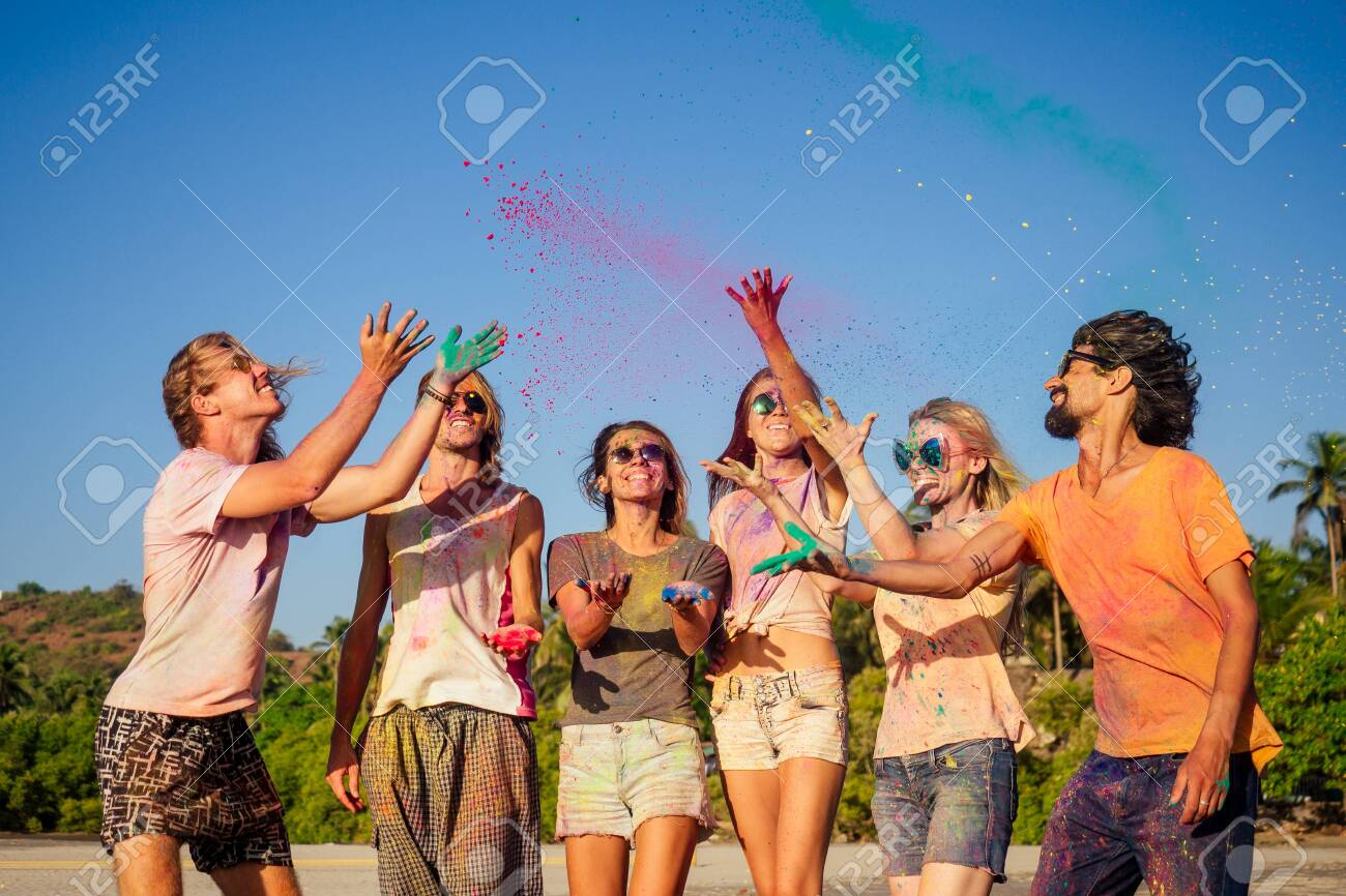 mixed race friends having fun with colors on seaside outdoors in Goa India - 146075800