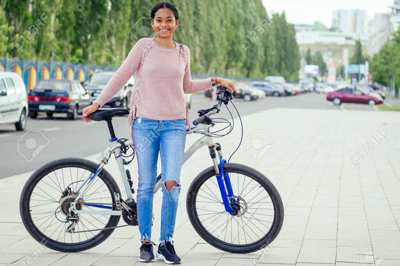 asian woman taking a a bicycle for a rent in downtown - 157366426