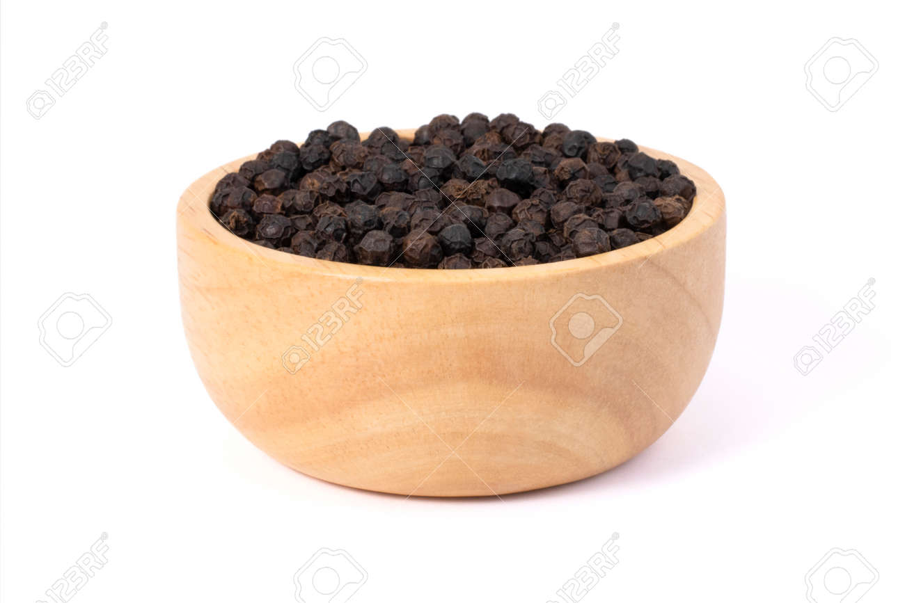 Closeup black pepper seeds or peppercorns ( dried seeds of piper nigrum) in wooden bowl isolated on white background. - 151367218