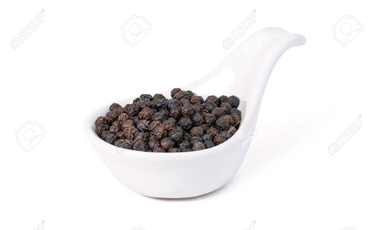 Closeup black pepper seeds or peppercorns ( dried seeds of piper nigrum) in ceramic spoon isolated on white background. - 152238831