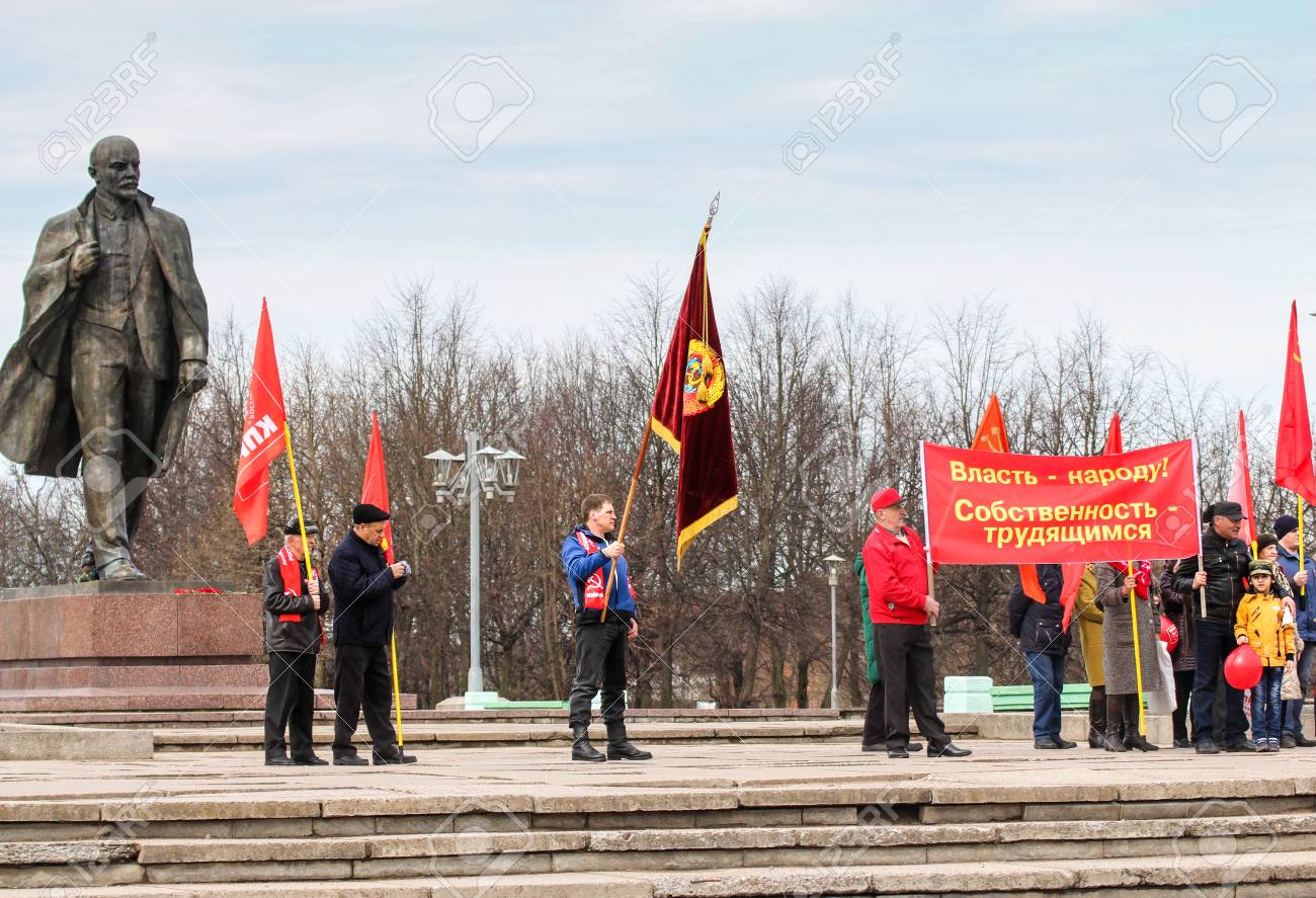 People with festive flags and banners near the monument to Lenin
