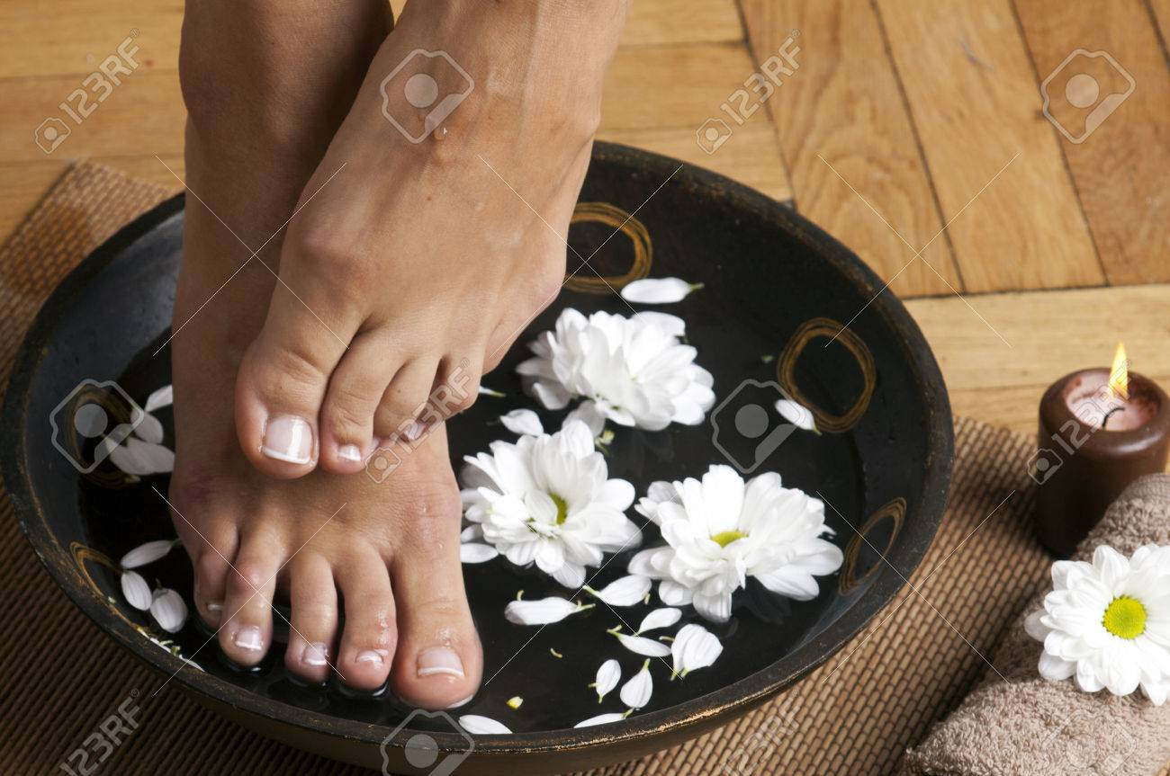 feminine feet in foot spa bowl with flowers towel and candle foto