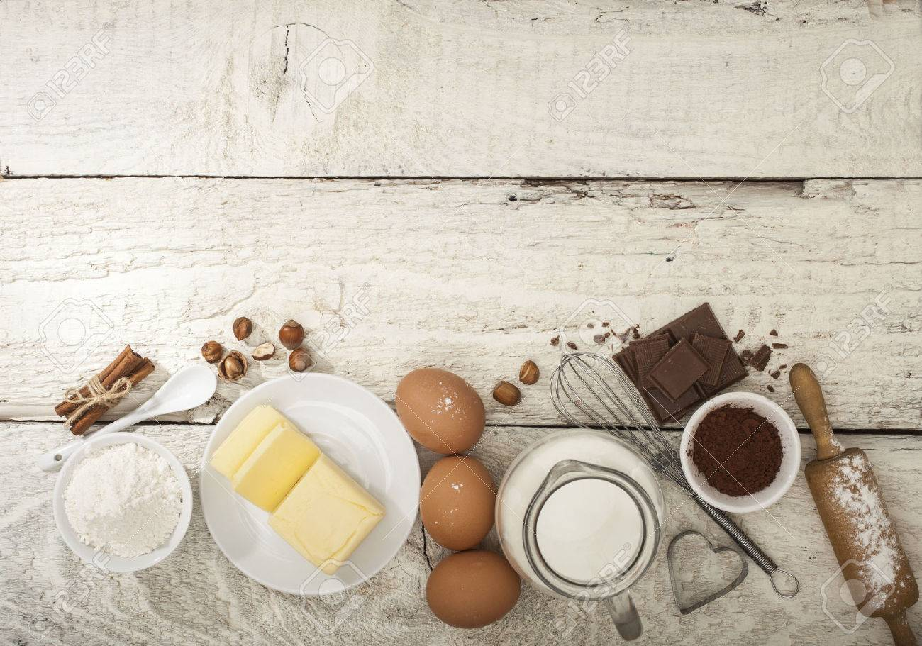 Ingredients for the preparation of bakery products: flour eggs butter milk chocolate cocoa nuts. Top view. Rustic style. White wooden background. - 51085614