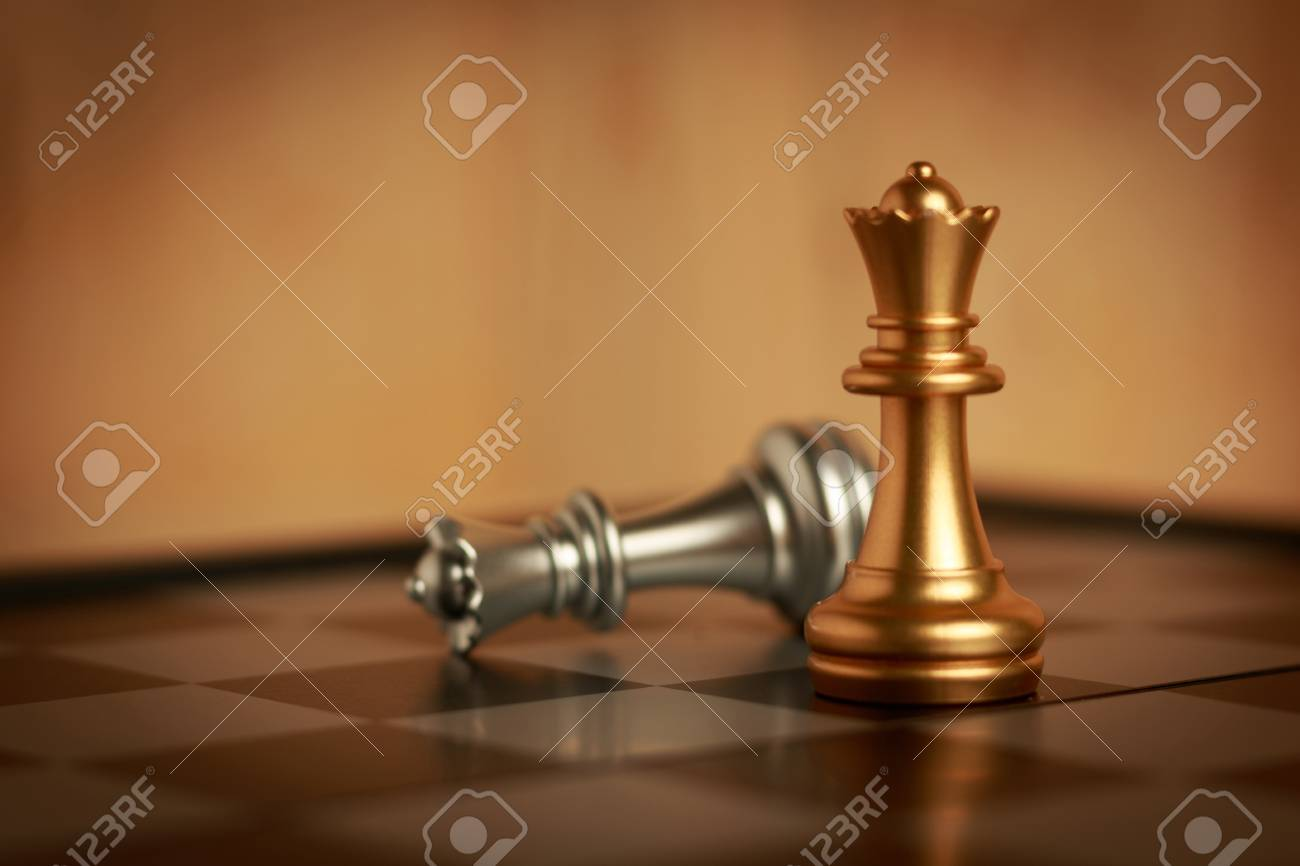 Two queen chess set on board. The gold is located and silver falls down. Select focus shallow depth of field and blurred background. Concept work and retro process - 101144367