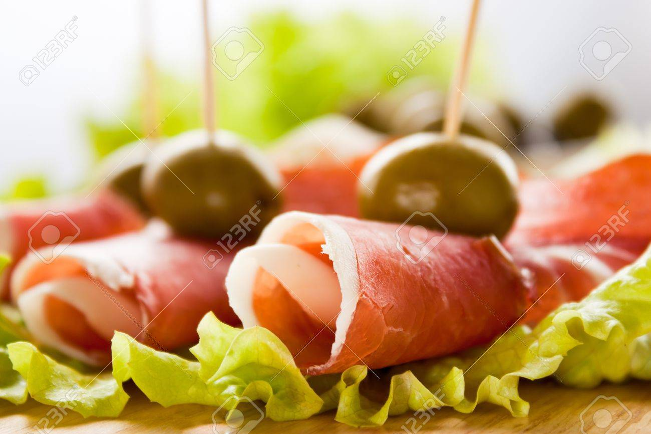 Slices of prosciutto rolled up and arranged on a lettuce leaf. Shallow depth of field. Stock Photo - 10635527