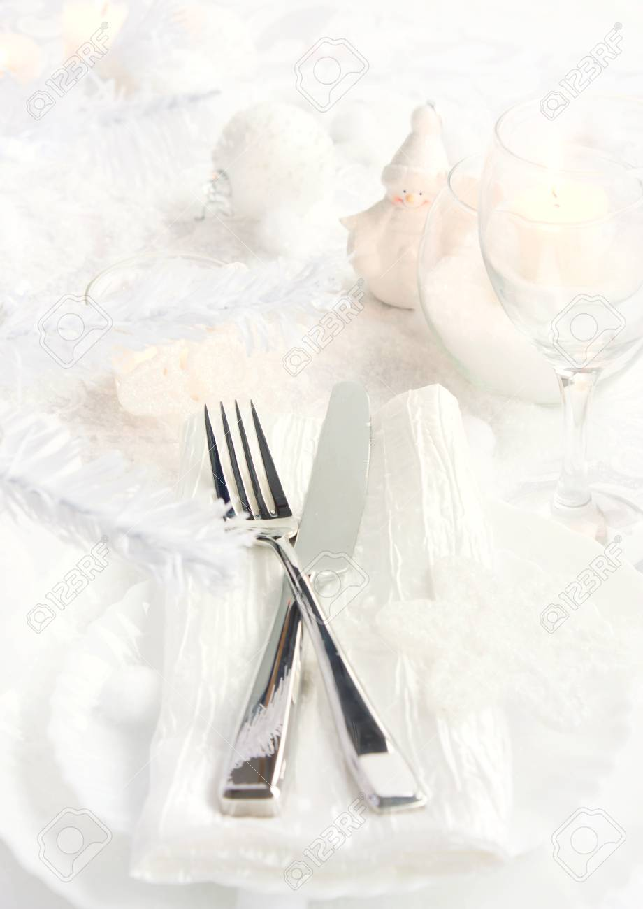 Restaurant series with copyspace. Christmas dinner with table setting in white and holiday ornaments Stock Photo - 11341632