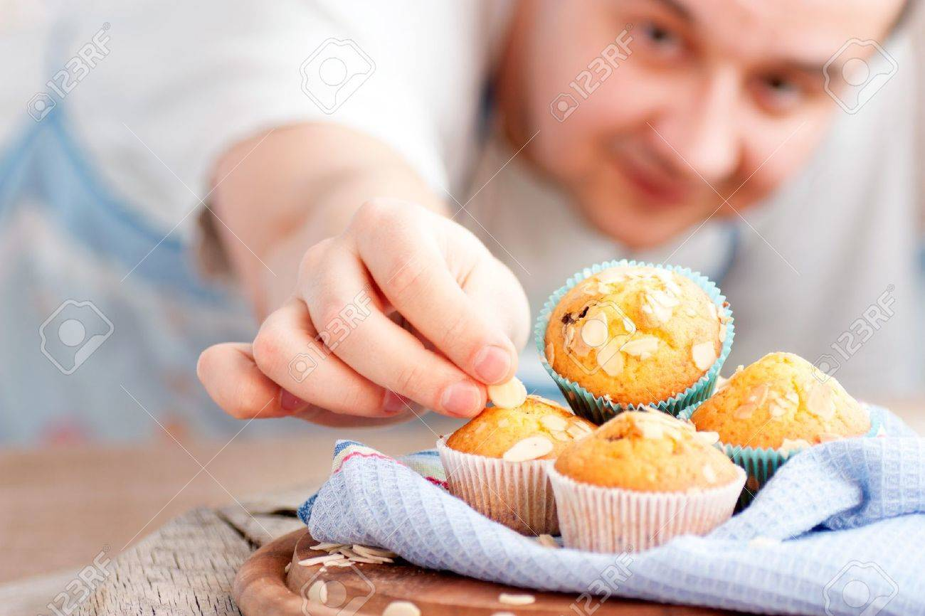 Chef is decorating delicious organic muffins Almond and cherry cup cakes in natural setting - 12812664