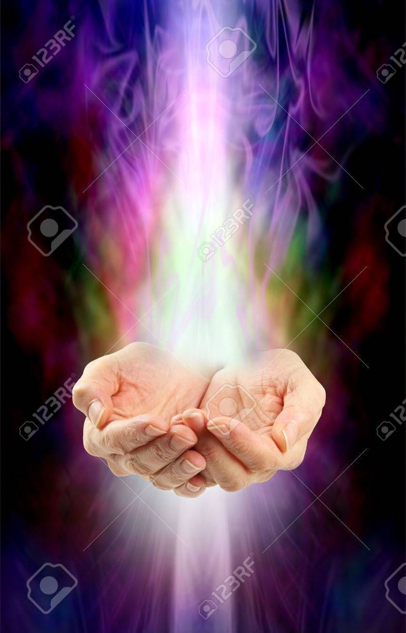 Receiving healing - Female cupped hands with white energy streaming in from above and below on a swirling misty multicolored ethereal energy background - 49292555