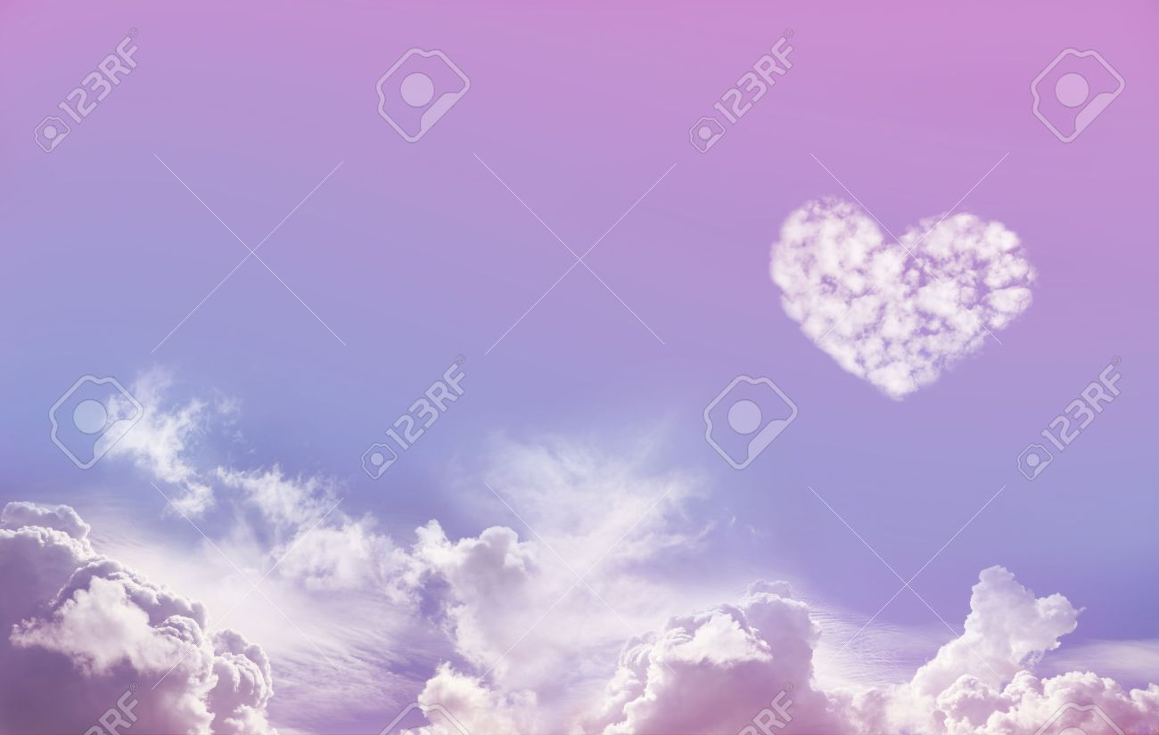 Love is in the Air - Wide Blue and Pink Sky Background with fluffy clouds along the bottom and one large isolated Love Heart Shaped cloud formation above on right hand side with plenty of copy space - 51396922