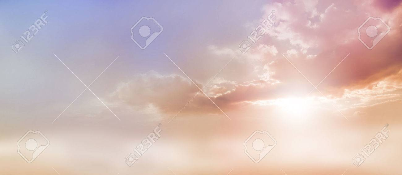 Dreamy Romantic Sky scape - beautiful wide peach and dusky pale blue sky and cloud scape with a burst of sunlight emerging from under the cloud base with plenty of copy space - 59328249