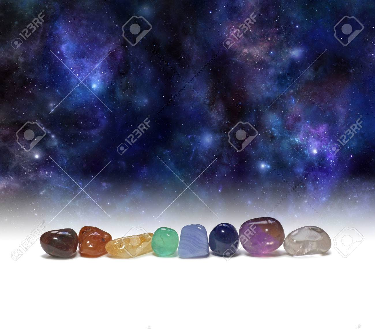 Cosmic Chakra Healing Stones - a row of chakra colored tumbled healing crystals set against a background of the Universe providing copy space above - 68540332