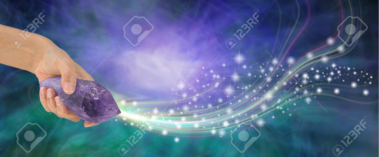 Massive Amethyst with beautiful energy - female hand holding large terminated amethyst quartz wand shooting out sparkles across a purple and jade energy background with copy space - 92413884