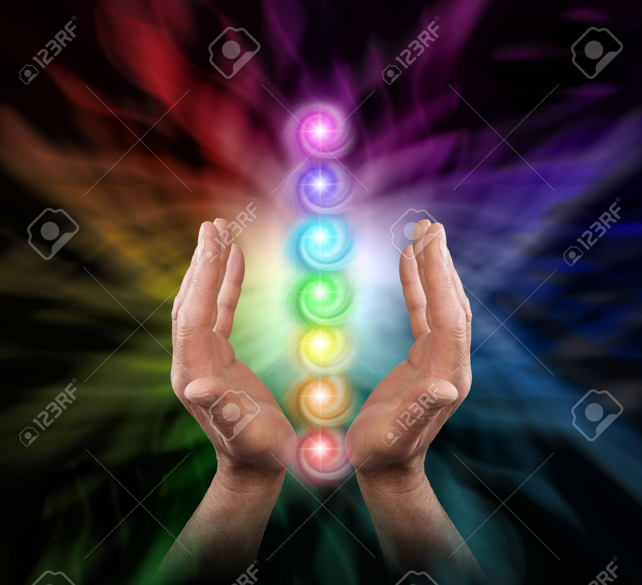 Sending Chakra Healing Energy - Male parallel hands facing upwards against a multicoloured background of energy and the Seven Chakras floating between his hands - 94913646