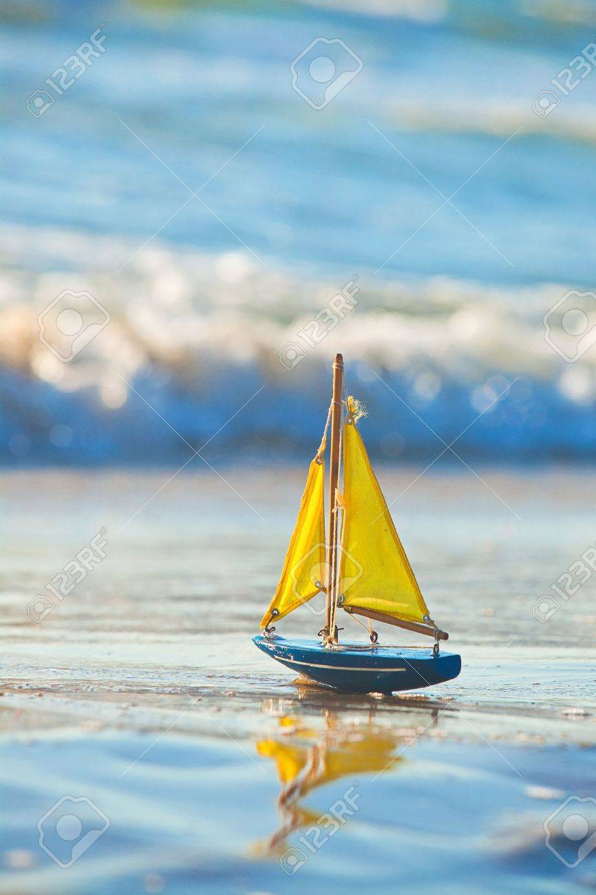 The little toy boat stands on sandy beach - 13282279