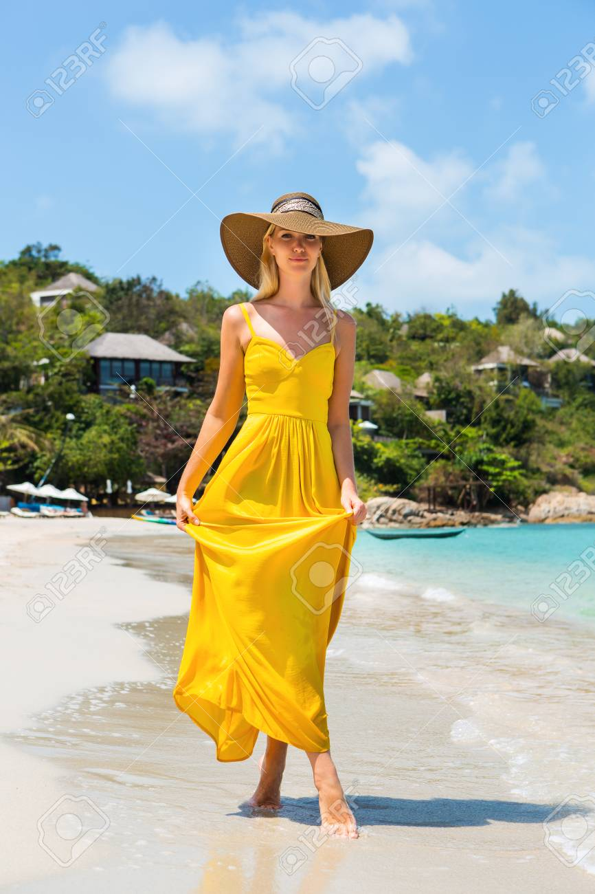 Carefree beautiful elegant blond girl in beach straw hat and long yellow  dress flying in the 443e0fc9622e
