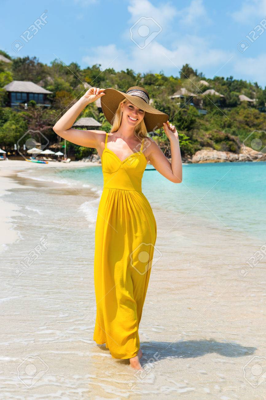 Carefree beautiful fashion blonde girl in beach straw hat and long yellow  dress flying in the 77d349151c60