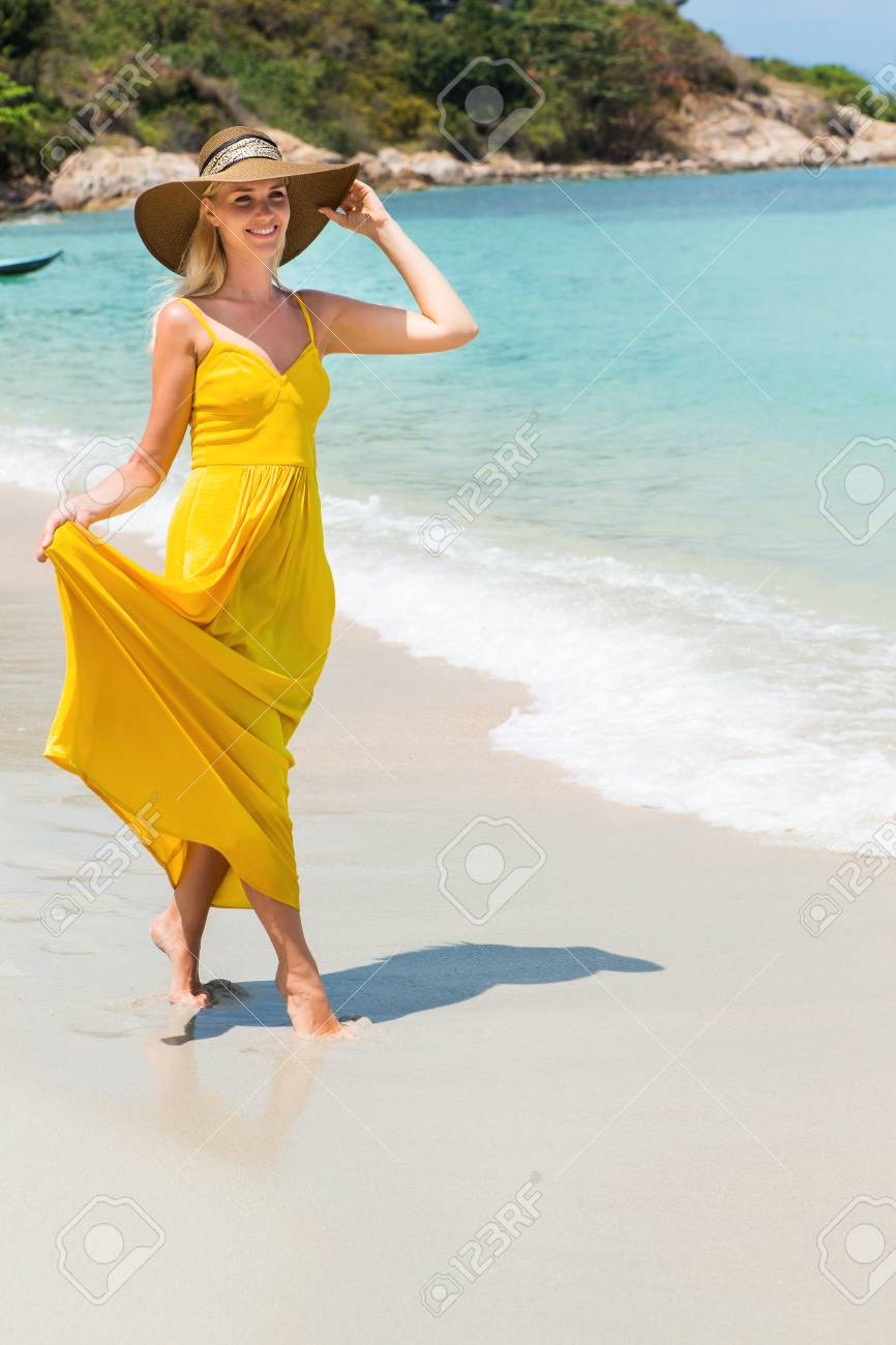 Carefree beautiful elegant blonde woman in beach straw hat holding her long  yellow dress and walking a4731f8e96bb