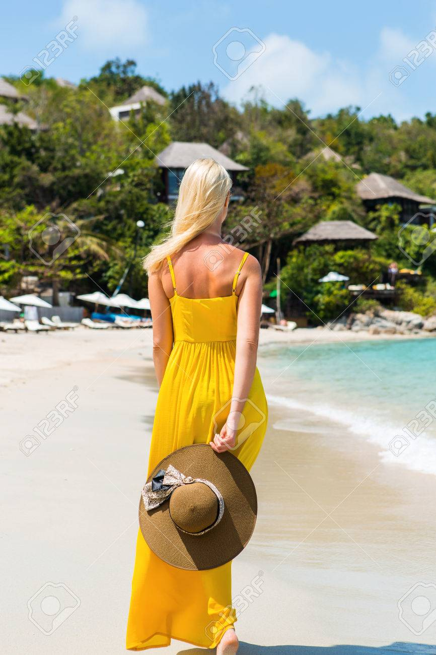 Carefree beautiful fashion blonde girl in long yellow dress flying in wind  walking barefoot by sand 5157dab53076