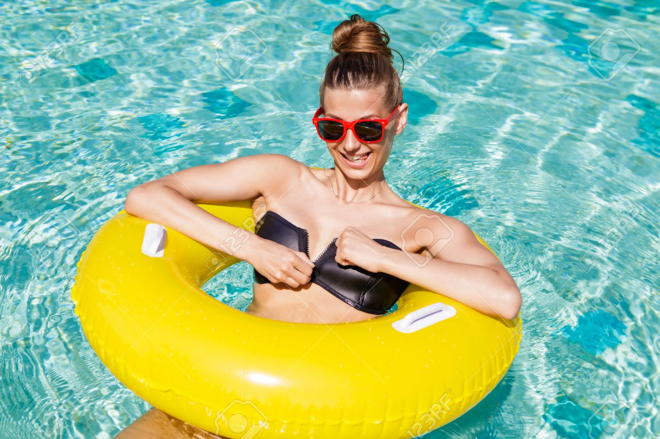 Amazing cute girl in sunglasses have fun at swimming pool party...