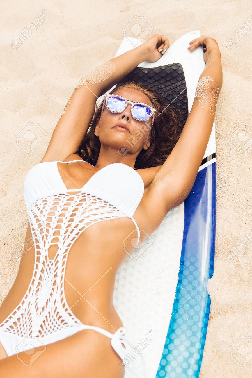 58bb1e2ced6a Mujer deportiva sexy en traje de baño bikini sensual y gafas de sol de moda  en la playa tropical acostado en la tabla hawaiana. La muchacha que ...