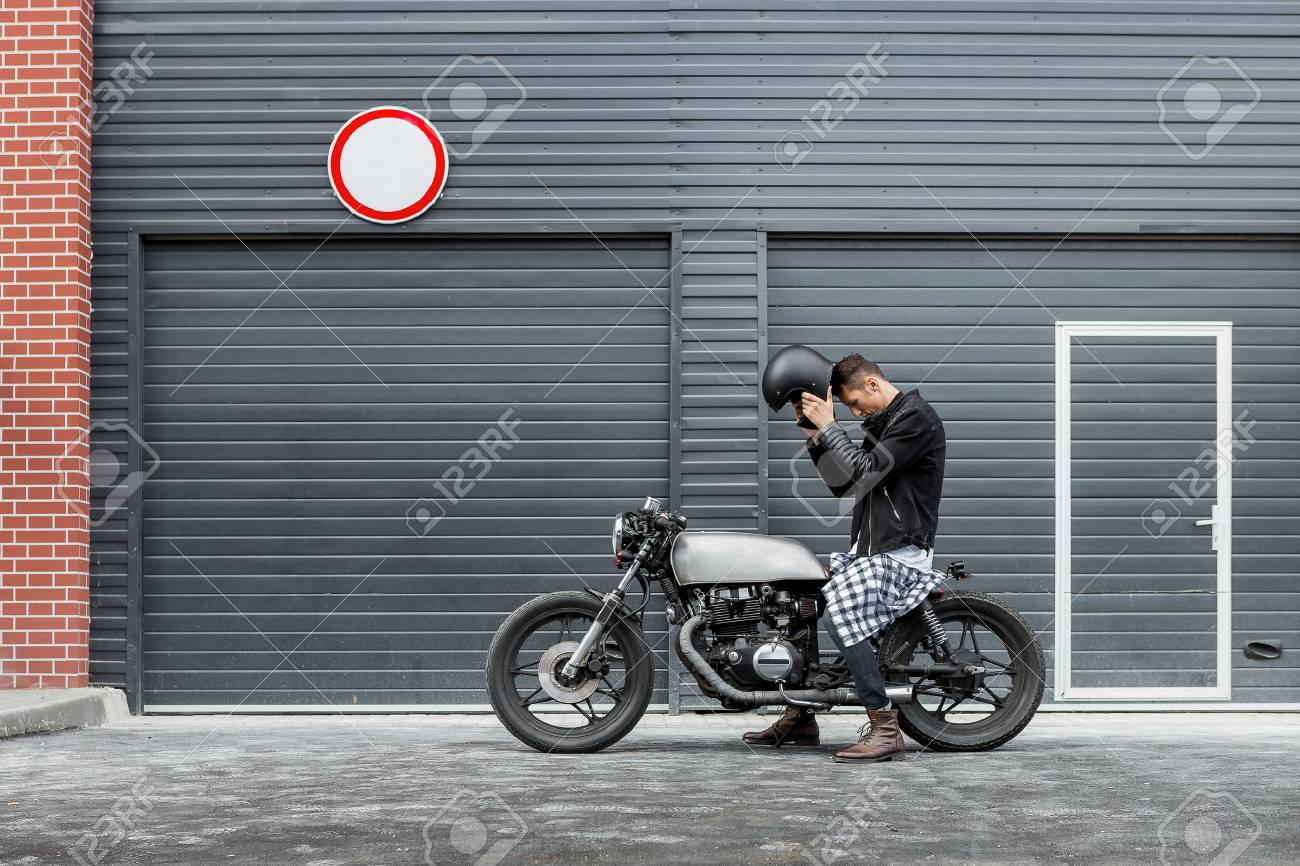 Handsome Rider Man Put On Black Biker Helmet While Sit Classic Style Cafe Racer Motorcycle