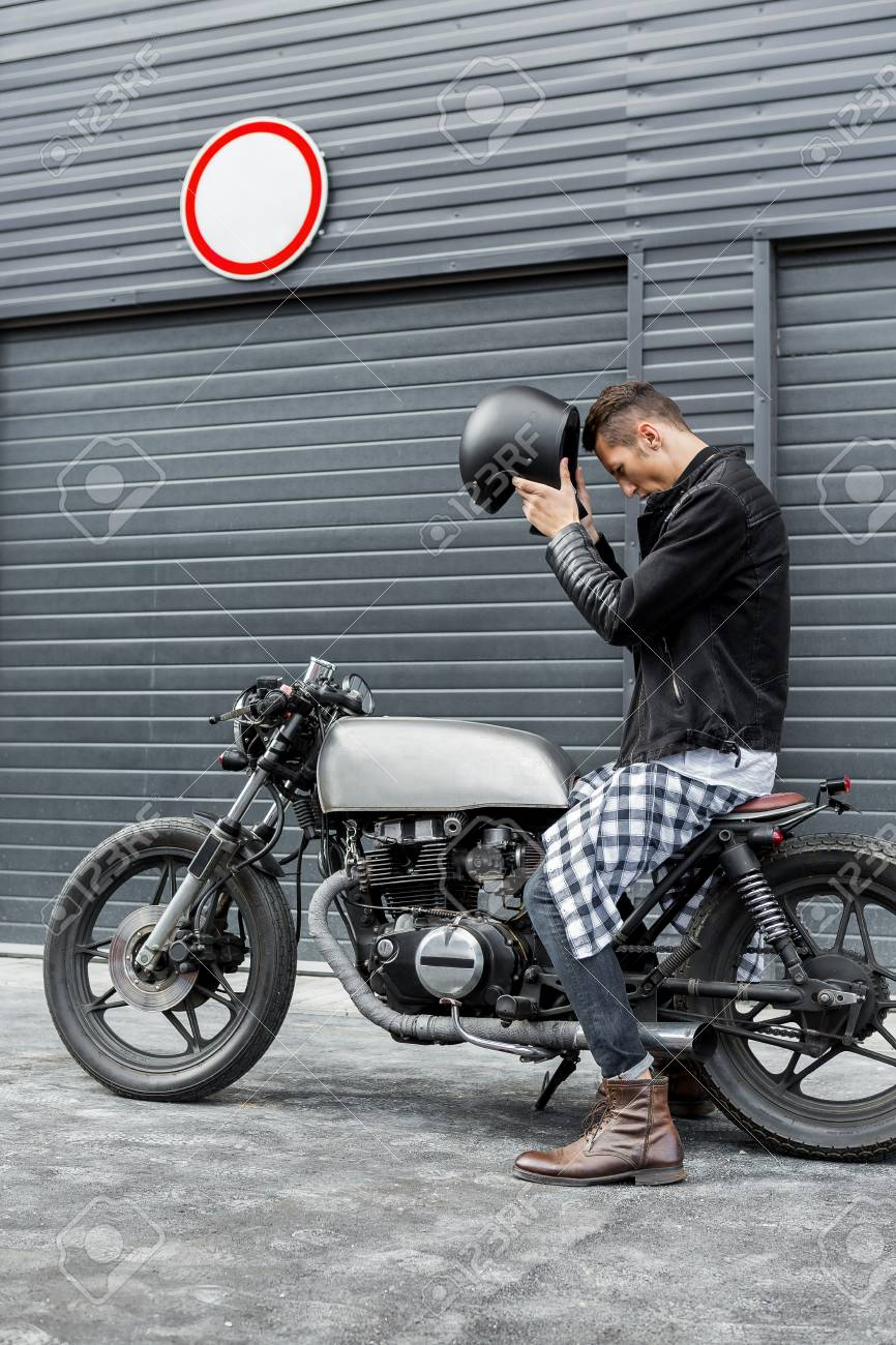 Handsome Rider Guy Take Off Black Biker Helmet While Sit On Classic Style Cafe Racer Motorcycle