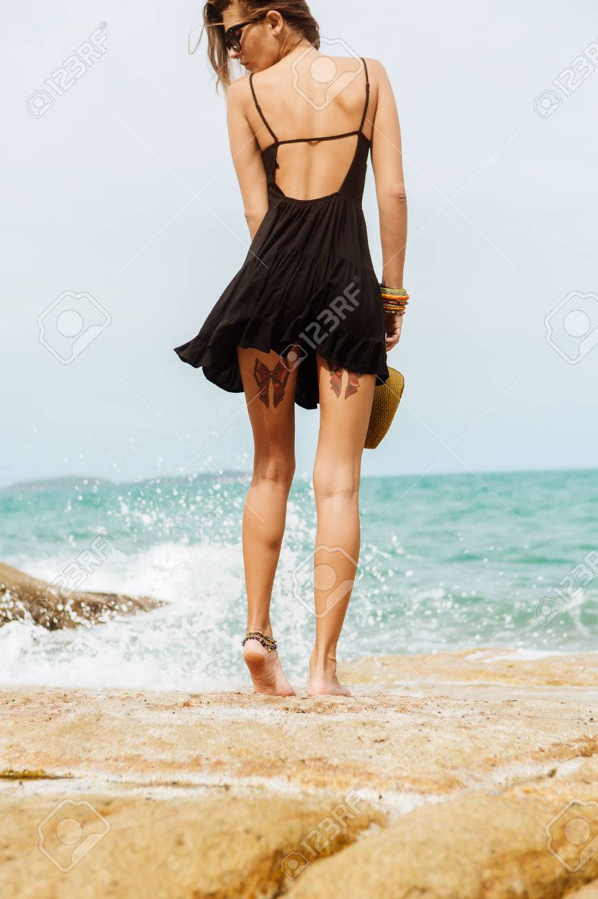 ce81007bec ... of a sexy woman in little black summer dress flying in the wind. View  from back. Beauty cute girl on a tropical beach sea ocean shore with large  stones.