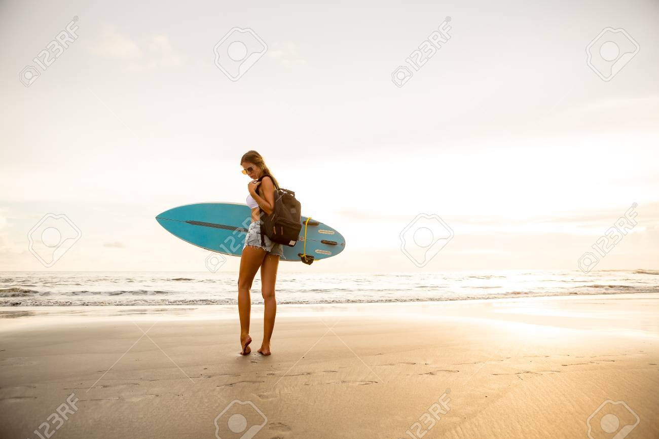 Young Surfer Woman In Sexy White Bikini With Surf Board And Travel