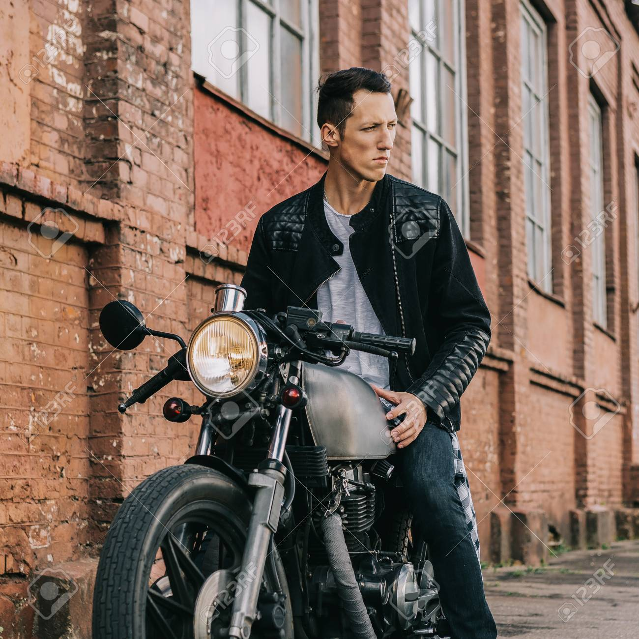 Handsome rider biker guy in leather jacket sit on classic style..