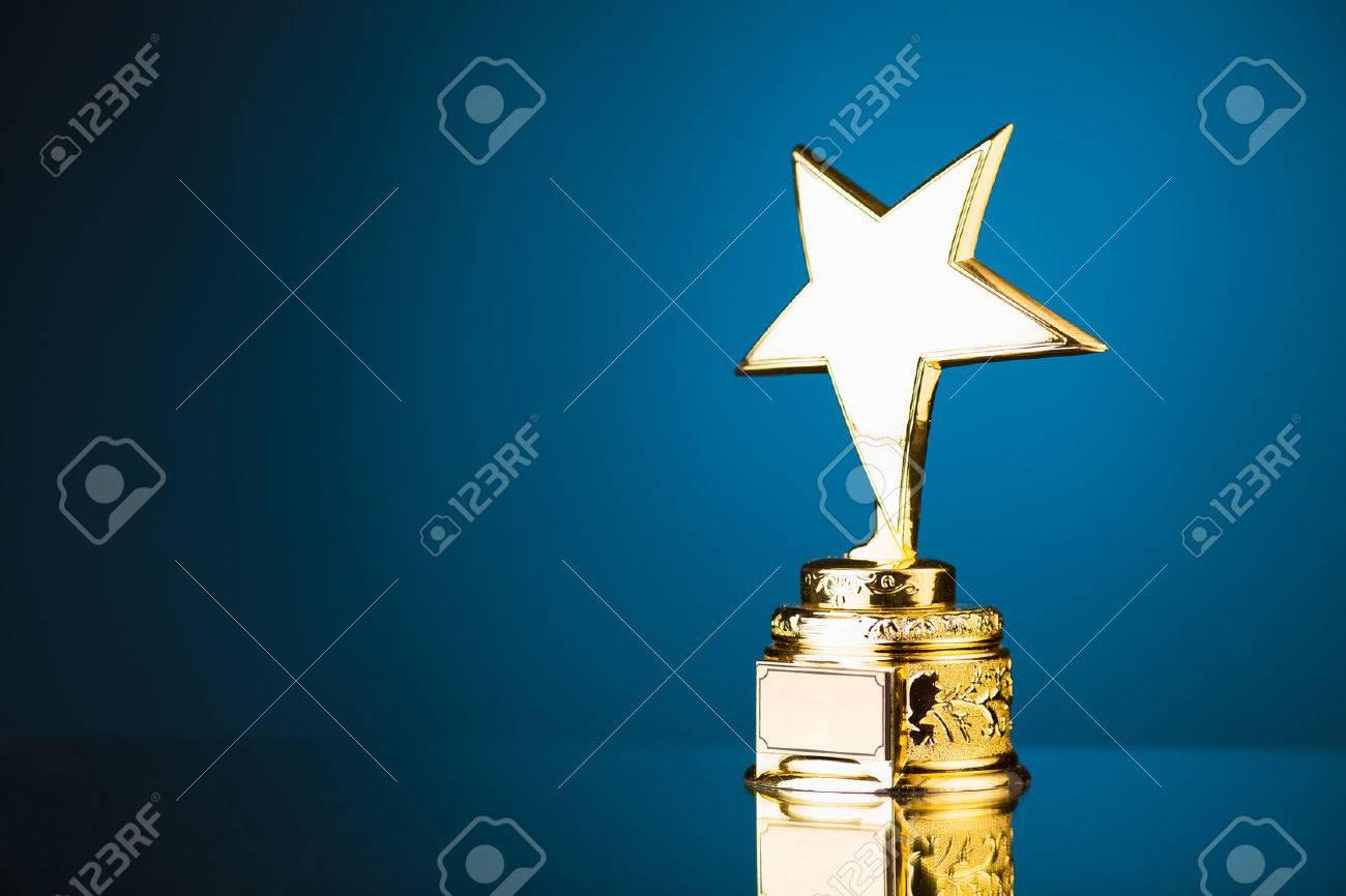 gold star trophy against blue background - 39569731