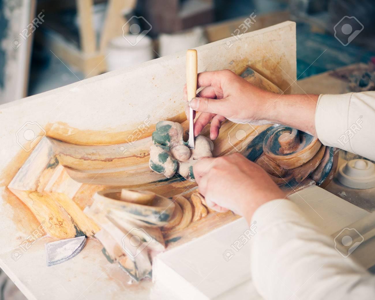 hands of restorer working with antique decor element - 42779046