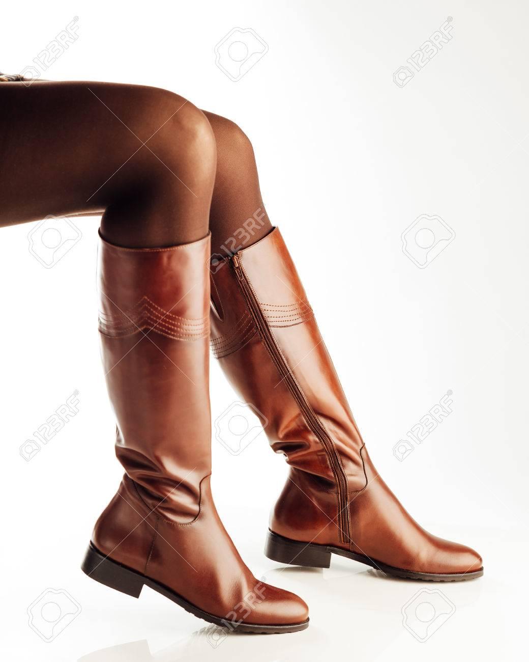 Piernas de la mujer con botas altas de cuero marrón, fondo blanco