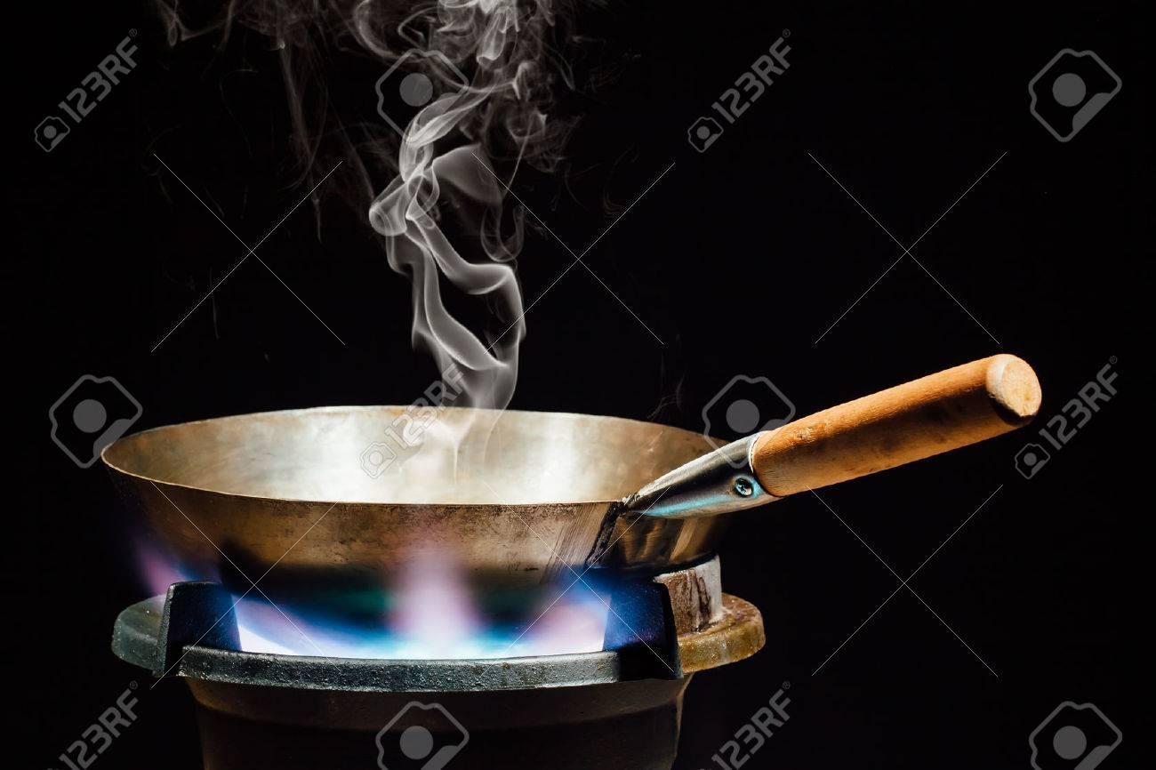 chinese wok pan on fire gas burner - 53615132